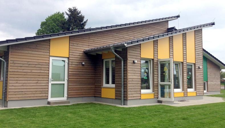 Fassadenmix aus horizontaler Holzverkleidung und farbigen Kunststoffplatten. Die Wände sind in Holzrahmenbauweise erstellt worden.