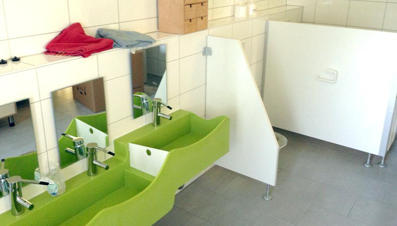 Innenansicht des Waschraumes mit einem Höhenversetzen Waschbecken für alle Altersgruppen und Schamwände der WC´s.